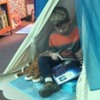 """A student using a station in our wellness center: This station is called """"Native Beach"""" and is equipped with a tee-pee, a turtle with blue lights and the sound of the ocean, and ocean-themed creatures, books and seashells"""