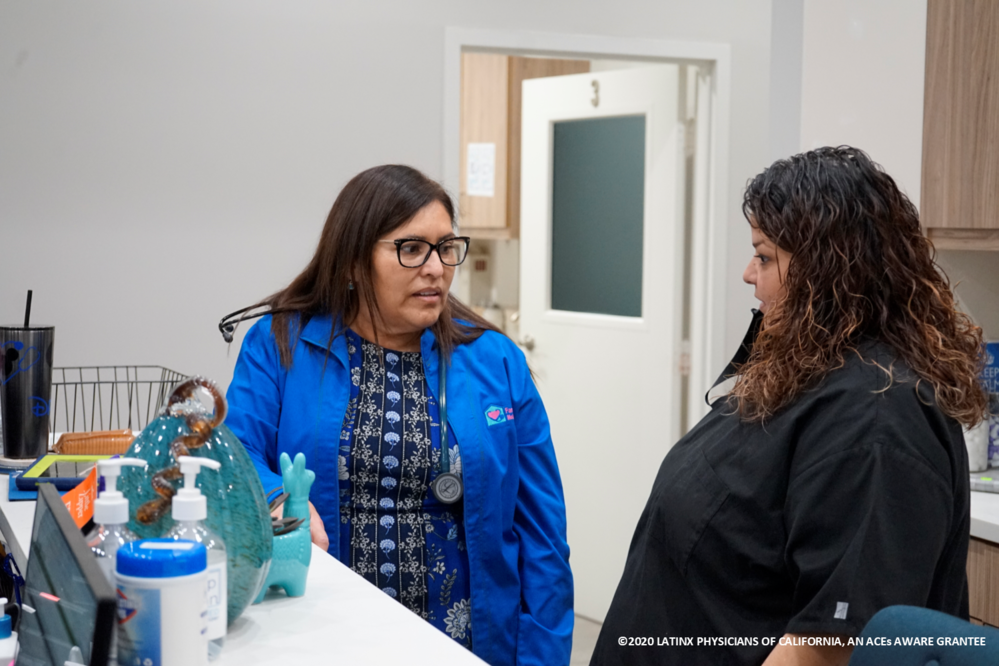 Latina Doctor Talking with Latina Patient at Appointment Desk, Post Appointment